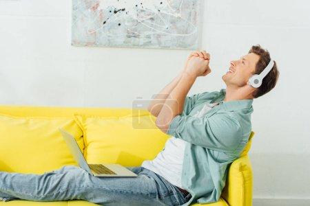 Photo pour Vue latérale de l'homme dans les écouteurs qui chante en tenant un ordinateur portable sur un canapé dans le salon - image libre de droit