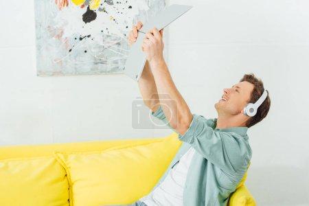 Photo pour Vue latérale d'un homme souriant dans un casque d'écoute tenant un ordinateur portable sur un canapé à la maison - image libre de droit