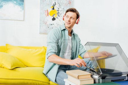 Smiling man in headphones looking away while using record player near books on coffee table