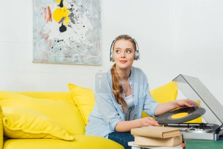 Photo pour Belle femme dans un casque détenant un disque vinyle près des livres et un tourne-disque sur le canapé dans le salon - image libre de droit