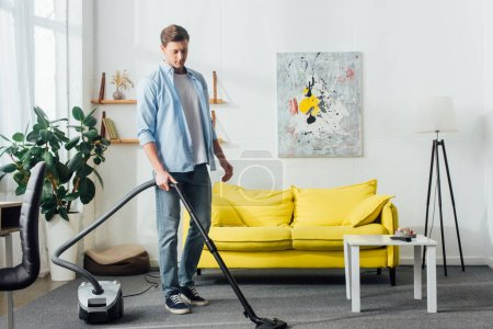 Photo for Man cleaning carpet with vacuum cleaner in living room - Royalty Free Image