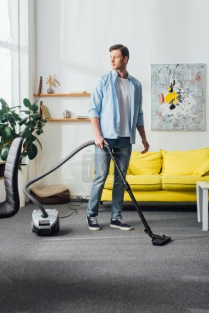 Photo for Handsome man looking away while using vacuum cleaner in living room - Royalty Free Image