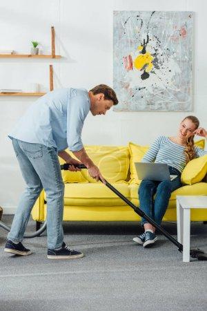 Photo pour Beau homme nettoyant tapis dans le salon près d'une femme souriante avec un ordinateur portable sur le canapé - image libre de droit
