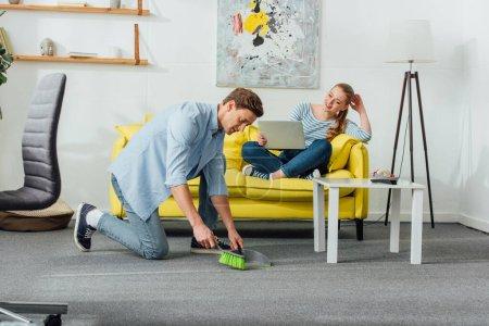 Photo pour Homme nettoyant tapis avec scoop et balai près d'une femme souriante avec ordinateur portable sur divan - image libre de droit