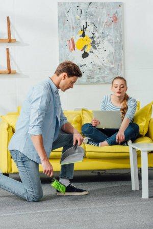 Photo pour Femme avec ordinateur portatif pointant du tapis à l'homme avec balai et balai dans le salon - image libre de droit