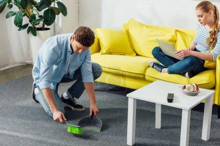 Photo pour Un homme nettoie un tapis avec une pelle et un balai près d'une amie en utilisant un ordinateur portatif sur un canapé - image libre de droit