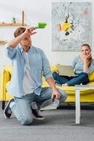 Photo pour Femme avec ordinateur portable regardant son petit ami fatigué avec balai et scoop dans le salon - image libre de droit