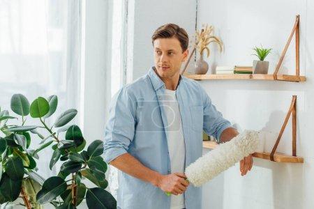 Photo pour Beau homme tenant brosse à poussière près des étagères avec des plantes et des livres dans le salon - image libre de droit