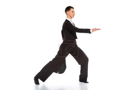 Photo pour Side view of elegant young ballroom dancer dancing on white - image libre de droit