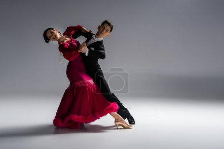 Photo for Elegant young couple of ballroom dancers in red dress in suit dancing on grey - Royalty Free Image