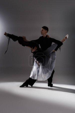 Photo pour Élégant jeune couple de danseurs de salon en tenue noire dansant dans l'obscurité - image libre de droit