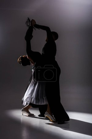 elegant young couple of ballroom dancers in black outfit dancing in dark