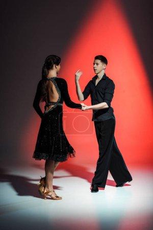 Photo pour Elegant young couple of ballroom dancers dancing in red light - image libre de droit