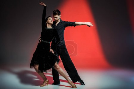 Photo for Elegant young couple of ballroom dancers dancing in red light - Royalty Free Image