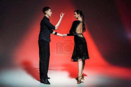 Photo pour Élégant jeune couple de danseurs de salon en tenues noires dansant en lumière rouge - image libre de droit