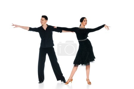 Photo pour Elegant young couple of ballroom dancers in black dress and suit dancing isolated on white - image libre de droit