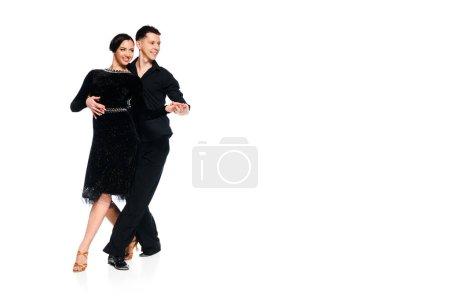 Photo pour Élégant jeune couple de danseurs de salon en robe noire et costume danse isolé sur blanc - image libre de droit