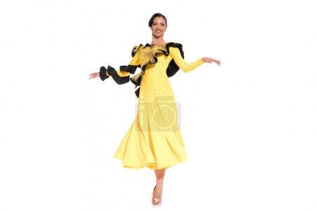 usmívající se elegantní mladá tanečnice ve žlutých šatech tanec izolované na bílém