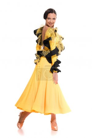 smiling elegant young ballroom dancer in yellow dress dancing isolated on white