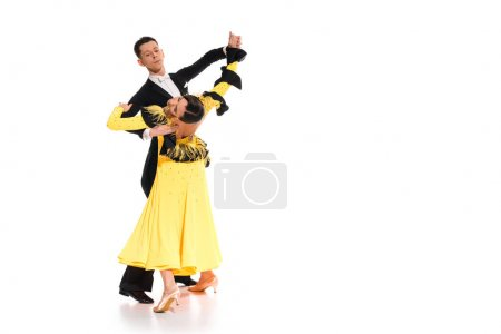 elegant young couple of ballroom dancers in yellow dress and black suit dancing on white