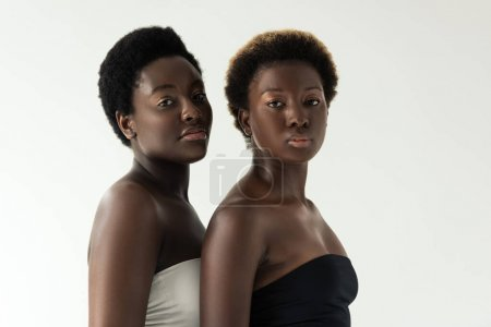 attractive african american girls in tops isolated on grey