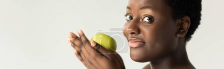 Photo for Panoramic shot of happy african american woman holding green apple isolated on grey - Royalty Free Image