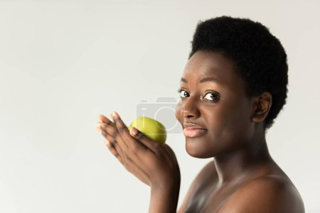 smiling nude african american woman holding green apple isolated on grey