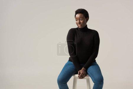 Photo pour Afro-américaine fille en jeans et col roulé noir assis sur tabouret isolé sur gris - image libre de droit