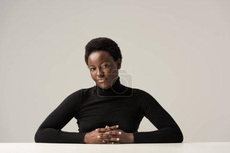 Foto de Hermosa mujer afroamericana en cuello alto negro sentada a la mesa aislada en gris - Imagen libre de derechos