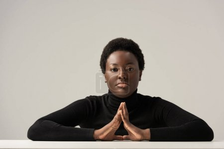 Photo for Thoughtful african american woman in black turtleneck sitting at table isolated on grey - Royalty Free Image