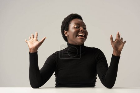 Photo for Excited african american woman in black turtleneck sitting at table isolated on grey - Royalty Free Image