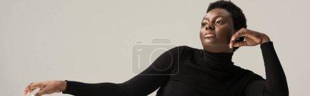 Foto de Plano panorámico de atractiva mujer afroamericana en cuello alto negro aislado en gris - Imagen libre de derechos