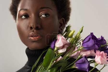 Foto de Mujer afroamericana en cuello alto negro sosteniendo flores de eustoma aisladas en gris - Imagen libre de derechos