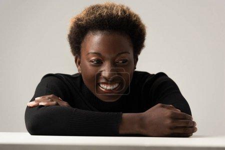 Photo pour Joyeuse femme afro-américaine au col roulé noir assise à table isolée sur gris - image libre de droit