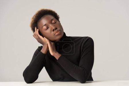 Foto de Atractivas mujeres afriamericanas tiernas con ojos cerrados en cuello negro sentado a la mesa aislada en gris. - Imagen libre de derechos