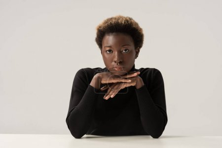 Photo for Pensive attractive african american woman in black turtleneck sitting at table isolated on grey - Royalty Free Image