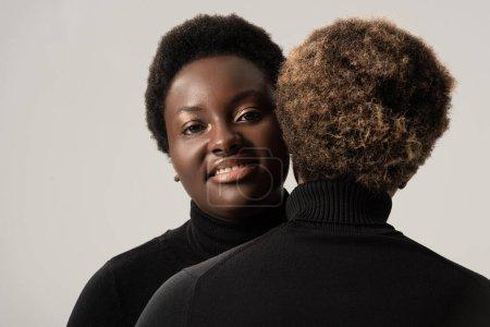 Foto de Sonrientes chicas afroamericanas en cuellos altos negros abrazándose aisladas en gris - Imagen libre de derechos
