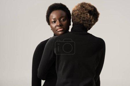 beautiful african american women in black turtlenecks hugging isolated on grey