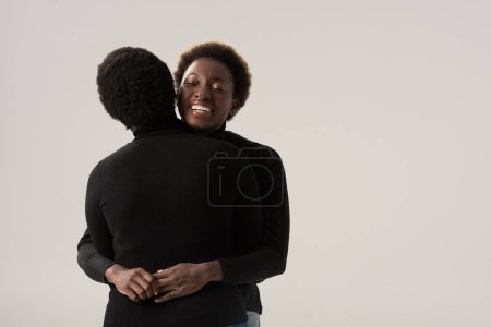 Foto de Alegre afroamericano novias en negro cuello alto abrazo aislado en gris - Imagen libre de derechos