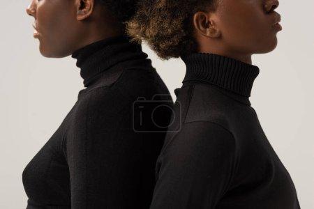 Foto de Vista recortada amigos afroamericanos en cuellos altos negros de pie espalda con espalda aislado en gris - Imagen libre de derechos