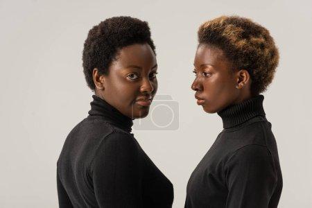 african american women in black turtlenecks isolated on grey