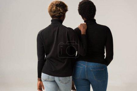 Foto de Vista posterior de amigos afroamericanos en cuellos altos negros aislados en gris - Imagen libre de derechos