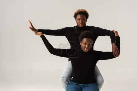 Photo for Female african american friends in black turtlenecks holding hands and gesturing isolated on grey - Royalty Free Image