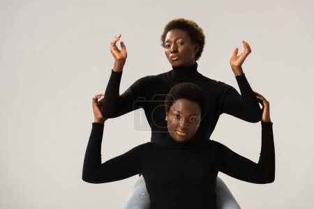 Foto de Mujeres afroamericanas amigas en cuellos altos negros gestos aislados en gris - Imagen libre de derechos