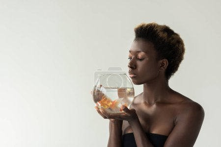 Photo for Attractive african american girl holding aquarium with fish isolated on grey - Royalty Free Image
