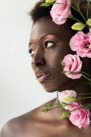 Foto de Hermosa chica afroamericana desnuda con flores de eustoma rosa aisladas en gris - Imagen libre de derechos