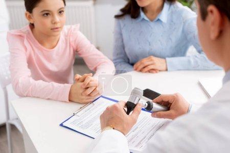 Photo pour Vue recadrée du médecin tenant l'otoscope près de la mère et de la fille attentive pendant la consultation - image libre de droit