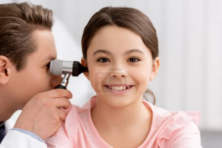Photo for Ent physician examining ear of cheerful kid with otoscope - Royalty Free Image
