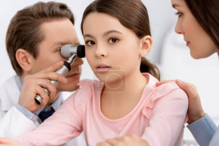 Photo for Cropped view of mother touching shoulder of cute daughter while otolaryngologist examining her ear with otoscope - Royalty Free Image