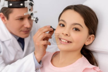 Photo for Attentive ent physician examining ear of smiling child with ear speculum - Royalty Free Image